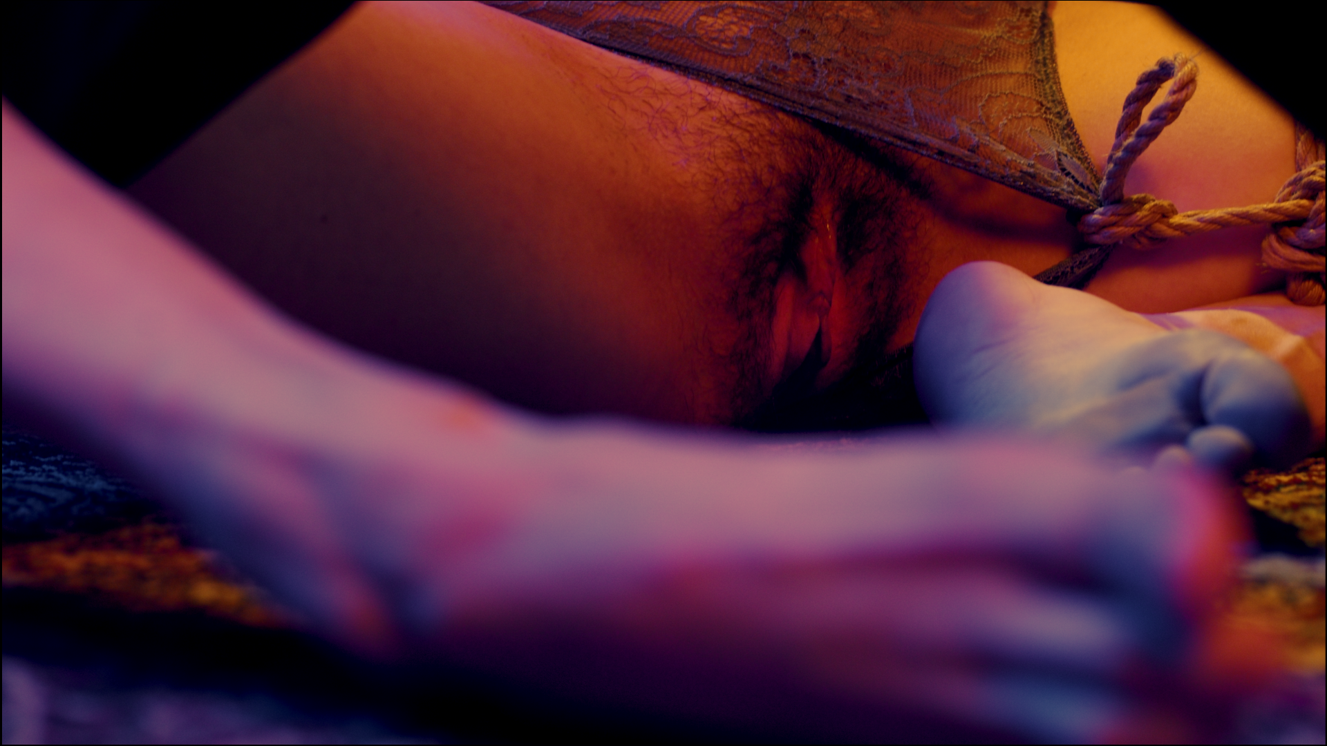 Close up of Nina's crotch as they sit with legs open, a shibari rope tied to their underwear pulling it to the side